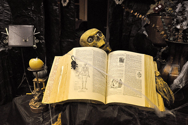 Wicked Spells: An old dictionary is repurposed as a spooky book of spells for Yvette Gallant's haunted house in Heritage Pointe. Gallant never buys props, instead opting to use what she can find in her or her friend's homes. (Photo by Centaine Tyler/The Press)