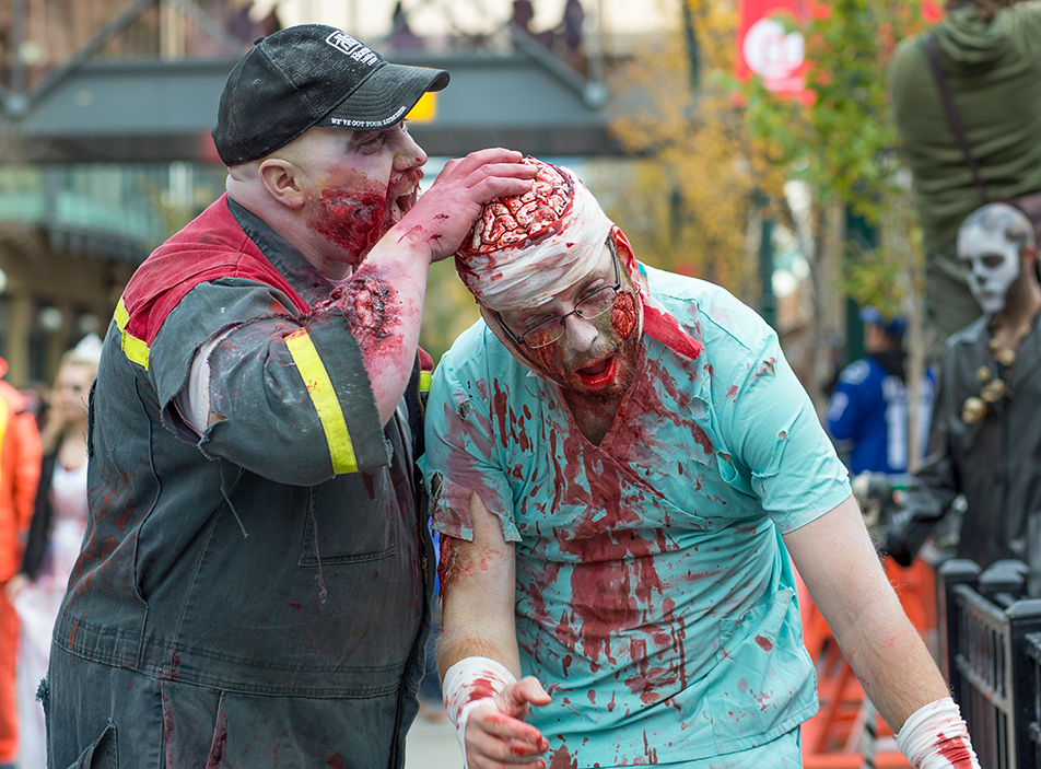 Zombie Apocalypse: A pair of zombies stop for a snack during the annual Zombie Walk down Stephen Ave in Calgary on Saturday, Oct. 12, 2013. (Photo by Jenn Sieppert/The Press)