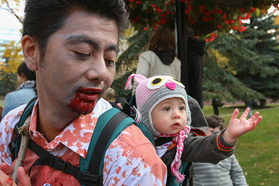 Zombie Apocalypse: Zombie dad's infant reaches out at the beginning of the Zombie Walk at Olympic Plaza in Calgary on Saturday, Oct. 12, 2013. Hundreds gathered for the walk, dressed in their scariest zombie costumes to parade down Stephen Ave. (Photo by Keith Marinier/SAIT Polytechnic)