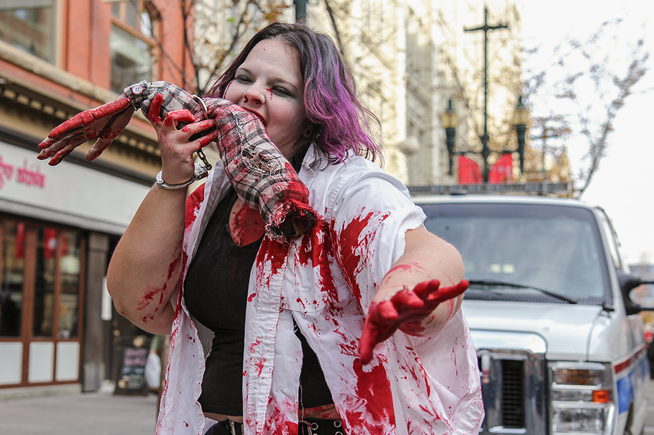 Zombie Apocalypse: Zombie Melissa Novak gnaws on an arm after escaping from the police. Taken during the Zombie Walk on Saturday, Oct. 12, 2013. Hundreds gathered for the walk, dressed in their scariest zombie costumes to parade down Stephen Ave. (Photo by Courtney Blatch/SAIT Polytechnic)