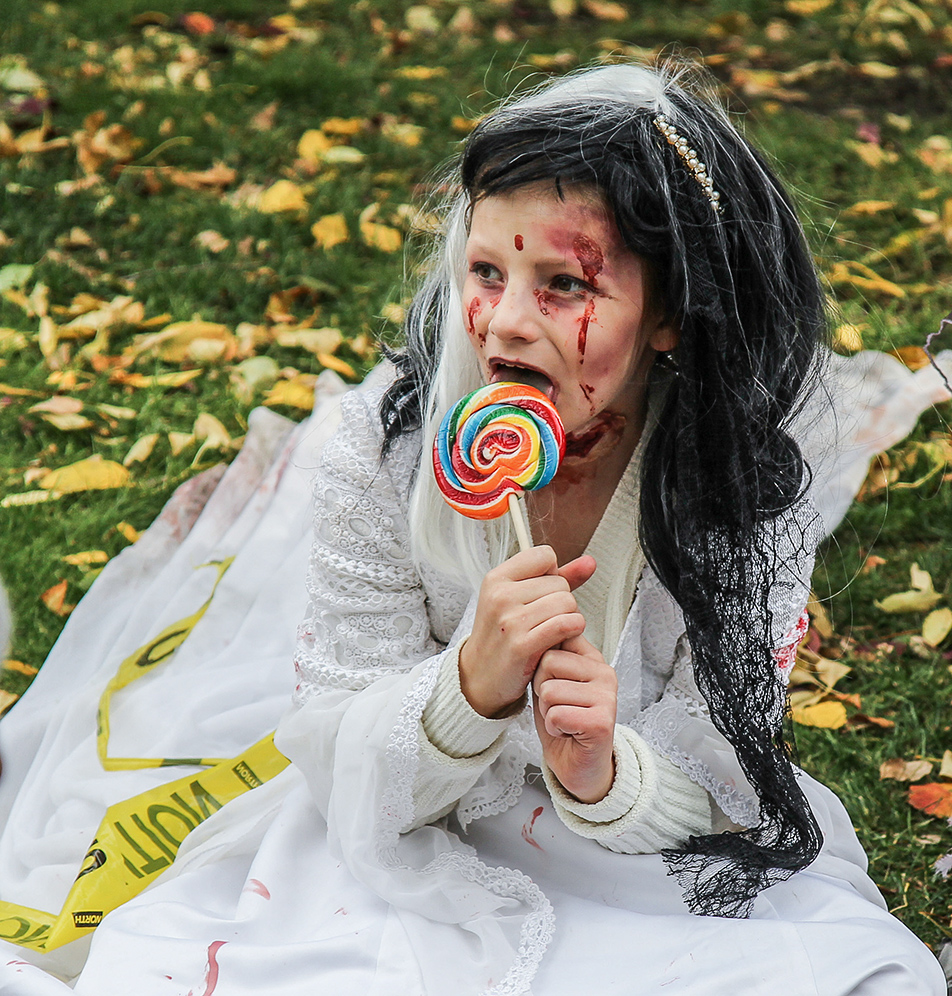 Zombie Apocalypse: Hannah Preston takes a break from being a zombie to eat a sucker during the Zombie Walk on Saturday, Oct. 12, 2013. Hundreds gathered for the walk, dressed in their scariest zombie costumes to parade down Stephen Ave. (Photo by Courtney Blatch/SAIT Polytechnic)