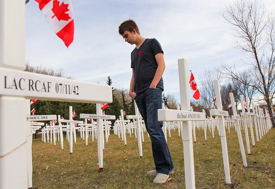 Quiet Moment: Garrett Evanson searches for his great grandfather's cross at the Field of Crosses Memorial Project on Saturday, Oct. 26, 2013. (Photo by Courtney Blatch/The Press)
