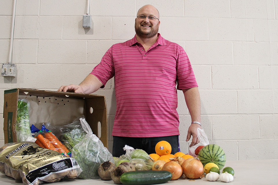 Good Food: Trevor Friesen, Good Food Box program manager, displays some of the fresh fruit and vegetables offered in the Good Food Box. (Photo by Chantal Hart/The Press)
