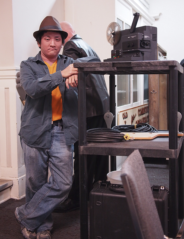 Filmmaker: Kaz Nagao stands beside a film projector that was used to play all of the films that were not digital at the event. (Photo by Leo Aragon/The Press)