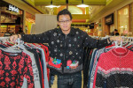 Tis the Season: Chris Cheng, one of the founders of Holiday Rejects, shows off the shop's collection of ugly sweaters. (Photo by Zehra Tajouri/The Press)
