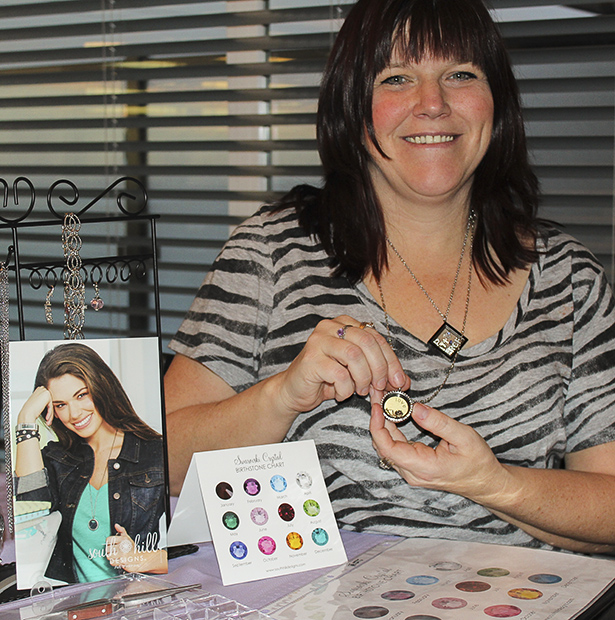 Booming Business: New to Canada, South Hill Designs is an innovative way to share your story in a customizable locket.Kerri Millard, an independent sales woman for South Hill, holds up one of her lockets at her home party in Chestermere, Alta. on Saturday, Jan. 18, 2014.  (Photo by Stefania Polga/The Press)