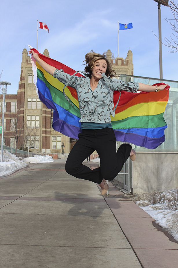 Jump for pride: SAITSA President, Tegan Cochrane hoists the pride flag in support of the LGBTQ community in front of Heritage Hall at SAIT Polytechnic in Calgary, on Thursday, Jan. 23, 2014. SAITSA is preparing for the upcoming pride awareness day on Feb. 12th. (Photo by Stefania Polga/The Press)