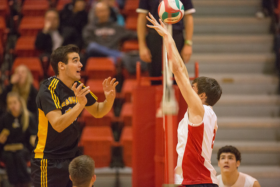 Tip: Olds College Broncos Ben Koch tips the ball over SAIT Trojans Brett Bolin's outstretched arms during men's volleyball action at the SAIT Campus Centre gym in Calgary on Thursday, Dec. 5, 2013. SAIT won the game easily in three sets. (Photo by Evan Buhler/The Press)