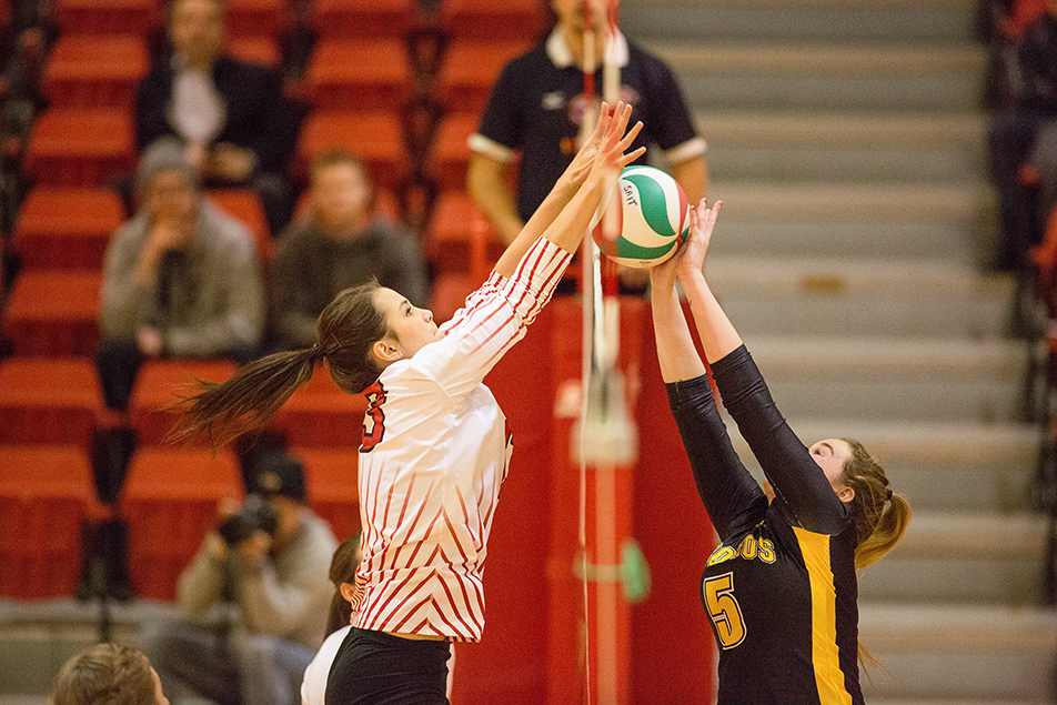 Going for the Block: SAIT Trojans Ellen Grundy, left,  blocks Olds College Broncos Jamie Craig at the net during women's volleyball action the SAIT Campus Centre gym in Calgary on Thursday, Dec. 5, 2013. The Trojans won the match in five close sets. (Photo by Evan Buhler/The Press)