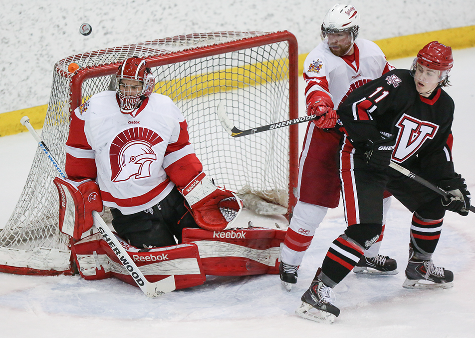 Big Save: The puck ricochets off of Trojans goaltender Brayden Hopfe as he makes the save against the Augustana Vikings at the SAIT arena in Calgary Saturday, Jan. 18, 2014. Hopfe, who won MVP, helped lead the Trojans to a 3-0 shut-out. (Photo by Crystal Schick/The Press)