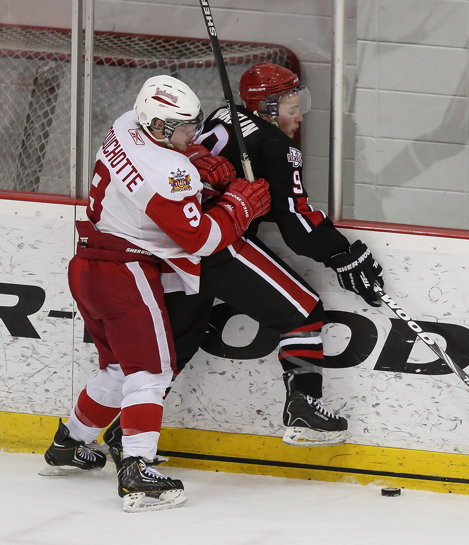 Big Hit: Nolan Souchotte, left, of the SAIT Trojans body checks Augustana Vikings' Boyd Wakelin into the boards during third period action at the SAIT arena in Calgary on Saturday, Jan. 18, 2014. The Trojans shut-out the Vikings 3-0. (Photo by Crystal Schick/The Press)