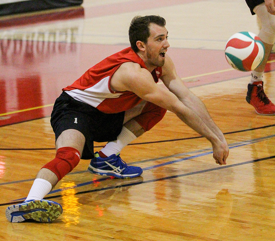 Big Dig: SAIT Trojans Brady Harder digs up the ball during a volleyball match against the Augustana Vikings at the Campus Centre gym at SAIT on Friday, Jan. 10, 2014. The Trojan's lost the match two sets to three. (Photo by Adelle Ellis/The Press)