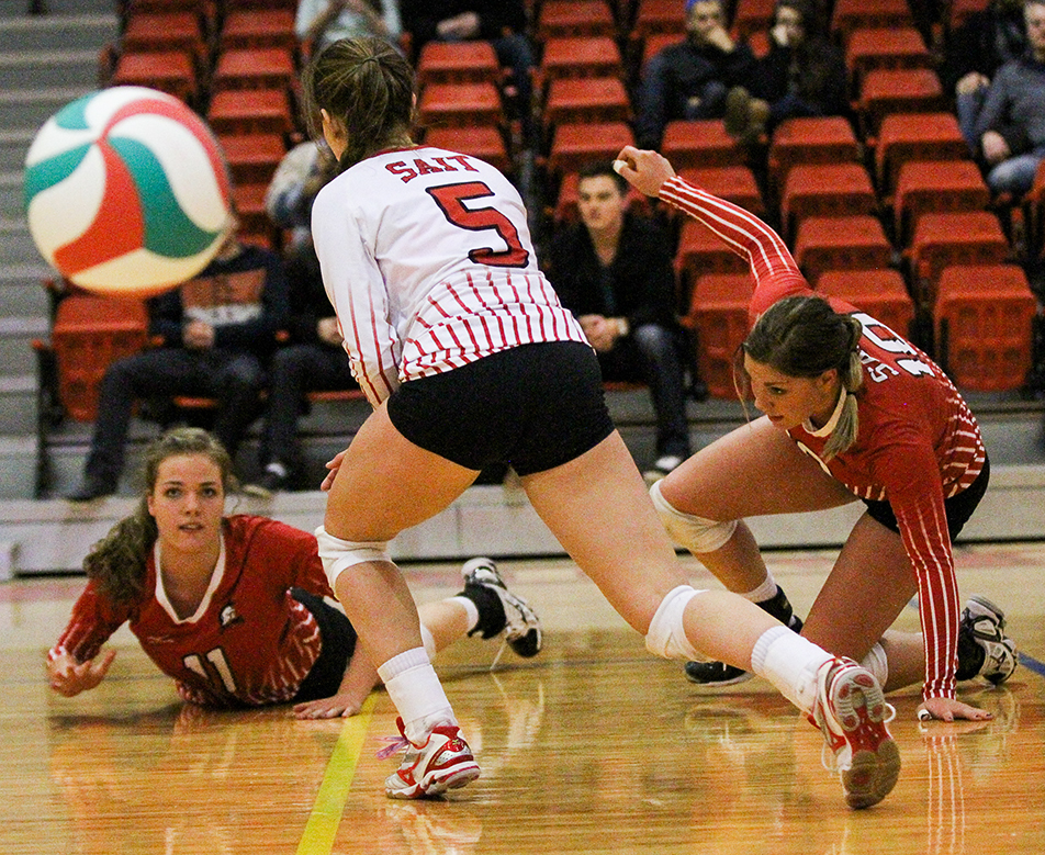 Scramble: SAIT Trojans Danika Ferguson, left, Kayla Nixon, and Alex Pasemko all dive for the ball during a matchup against the Augustana Vikings at the Campus Centre gym at SAIT in Calgary on Friday, Jan. 10, 2014. The Trojans defeated the Vikings three sets to one.(Photo by Adelle Ellis/The Press)