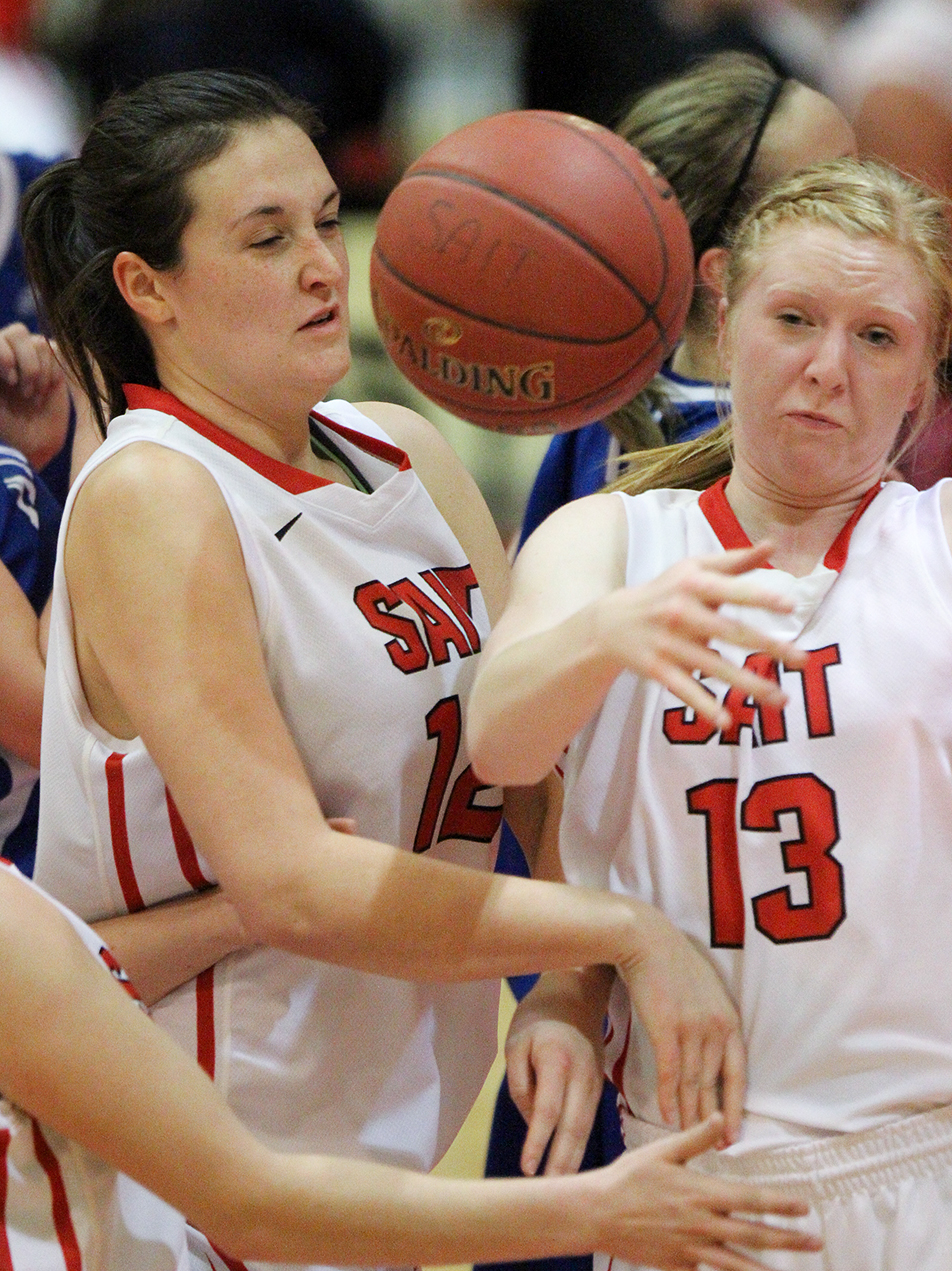 Eye on the Ball: SAIT Trojans Elyssa Sommerfeldt, left, and Jasmine Bergen-Henengouwen struggle to figure out the location of the ball during a matchup against the King's Eagles at the SAIT Campus Centre gym in Calgary on Friday, Jan. 17, 2014. The Trojans defeated the Eagles 70-29. (Photo by Laura Wilms/The Press)
