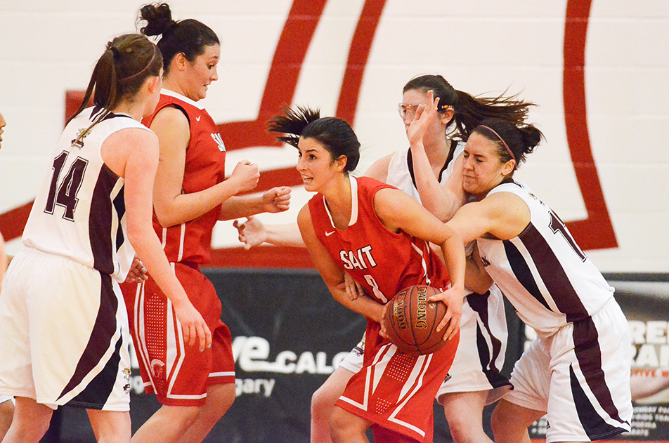 Protecting the Ball: SAIT Trojans Women's Basketball player Alexandra Bean protects the ball during a contest against the MacEwan Griffins at the SAIT gymnasium in Calgary on Sunday, Jan. 12, 2014. The Griffins won the game by a final score of 42-67. (Photo by Erin Knutson/The Press)