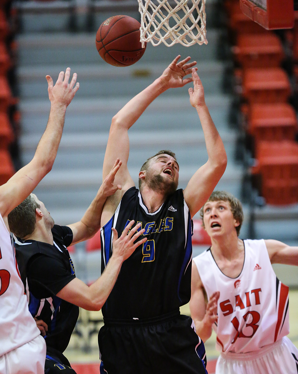 Blocked Kings Eagles player Mackenzie Andrews Stobart, middle, tries to block SAIT Trojans' Curtis Elaschuk during the men's basketball action at the SAIT gymnasium in Calgary on Friday, Jan. 17, 2014. The Trojans defeated the Eagles 83-72. (Photo by Courtney Blatch/The Press)