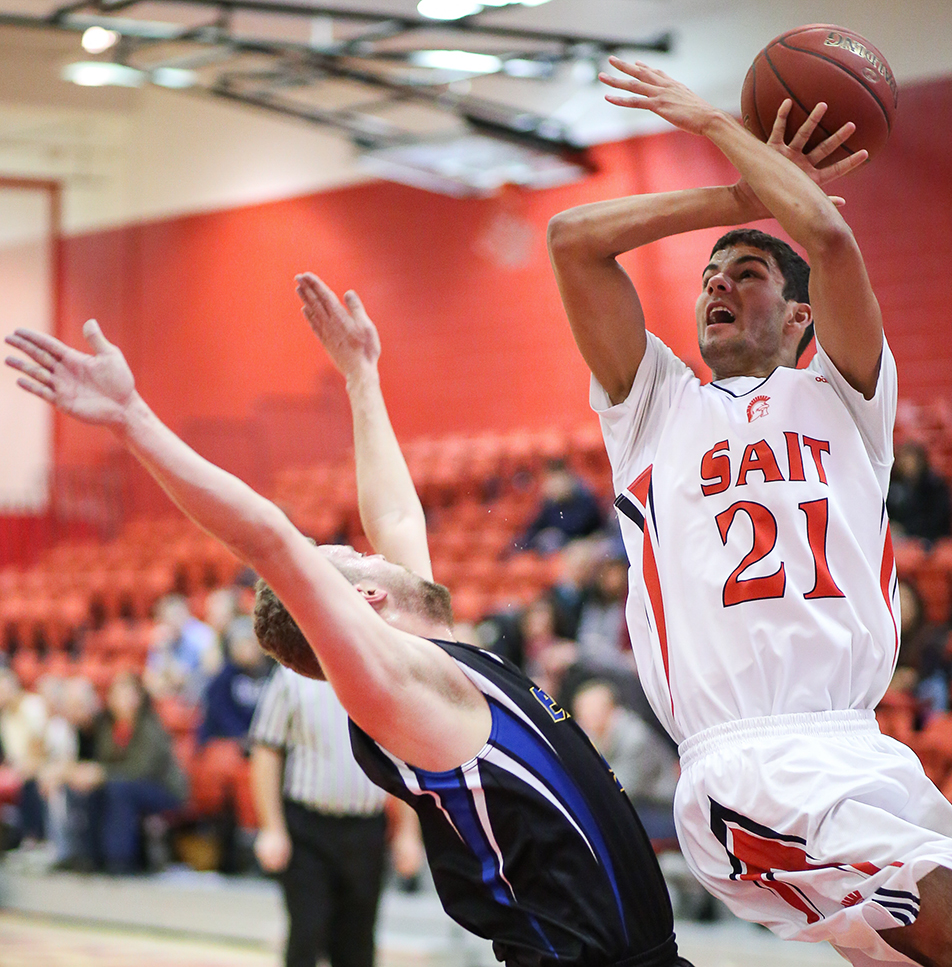 Big BlockSAIT Trojans player Mitchell Dass, right, jumps to block the ball from a King's Eagles offender during men's basketball action at the SAIT gymnasium in Calgary on Friday, Jan. 17, 2014. The Trojans defeated the Eagles 83-72. (Photo by Courtney Blatch/The Press)