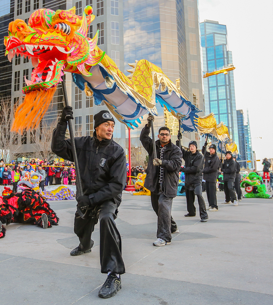 Traditional Dance: Ken Leong, left, and the Canadian Honan Shaolin Wushu Association perform their dragon dance in front of the Chinese Cultural Centre. (Photo by Courtney Blatch/The Press)