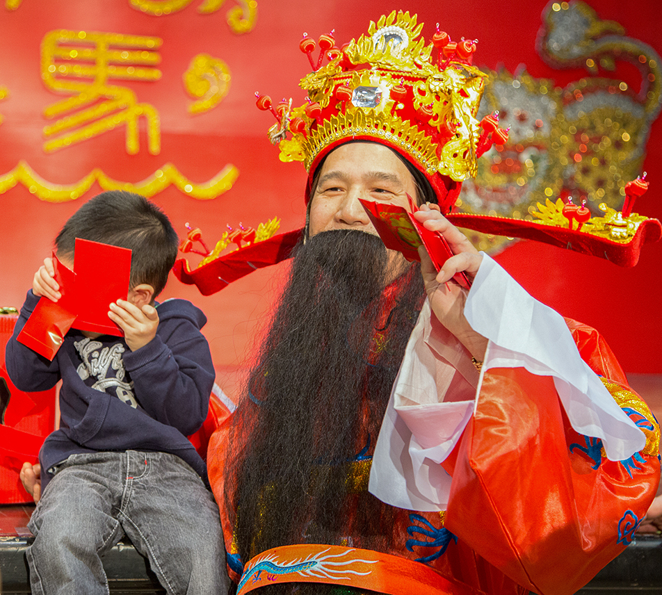 Peek a Boo: The God of Fortune offers gifts, good fortune and photo ops to anyone willing to have their picture taken - or not - during Chinese New Year celebrations.(Photo by Sarah Collins/The Press)