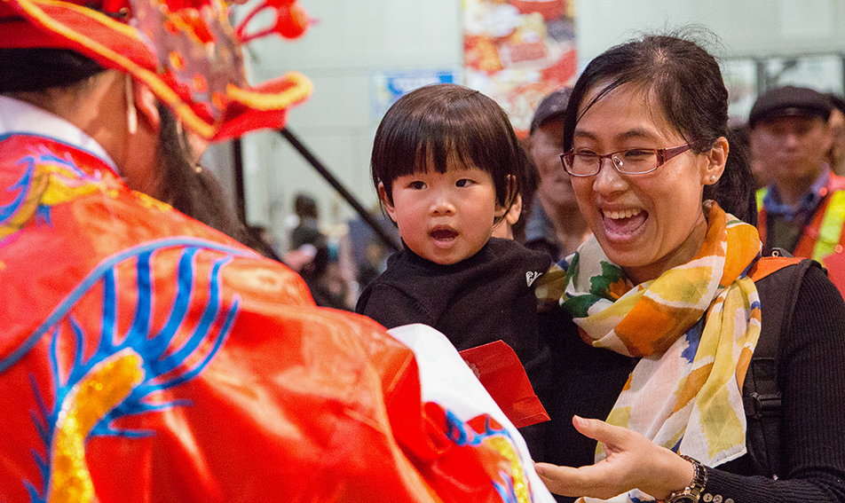 Colourful Costumes: Hundreds line up to receive a package from the God of Fortune after hours of performances and celebrations during Chinese New Year celebrations.  (Photo by Sarah Collins/The Press)