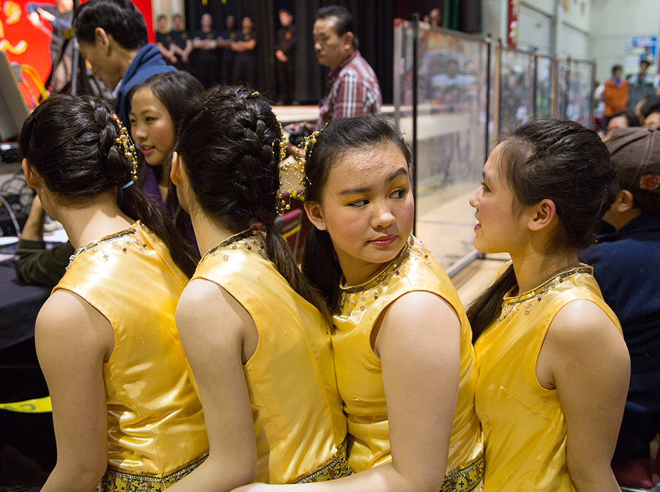 Tight Squeeze: Chinese fusion dancers make the best of the only chair available before heading onto the stage during Chinese New Year celebrations. (Photo by Sarah Collins /The Press)