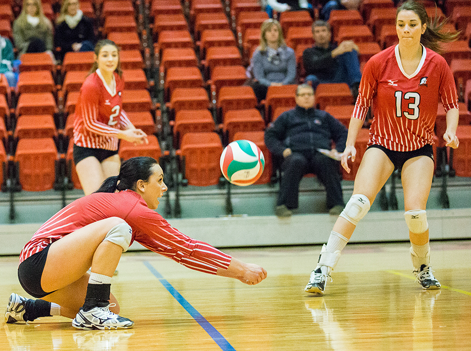 Big Dig: Trojan volleyball player Shantelle Jonasse, left, digs the ball during ACAC volleyball action agains the Lakeland Rustlers at SAIT's Campus Centre in Calgary on Saturday, Feb. 8, 2014. The Trojans lost the game in extra sets 5-4. (Photo by Phillip Currie/The Press)