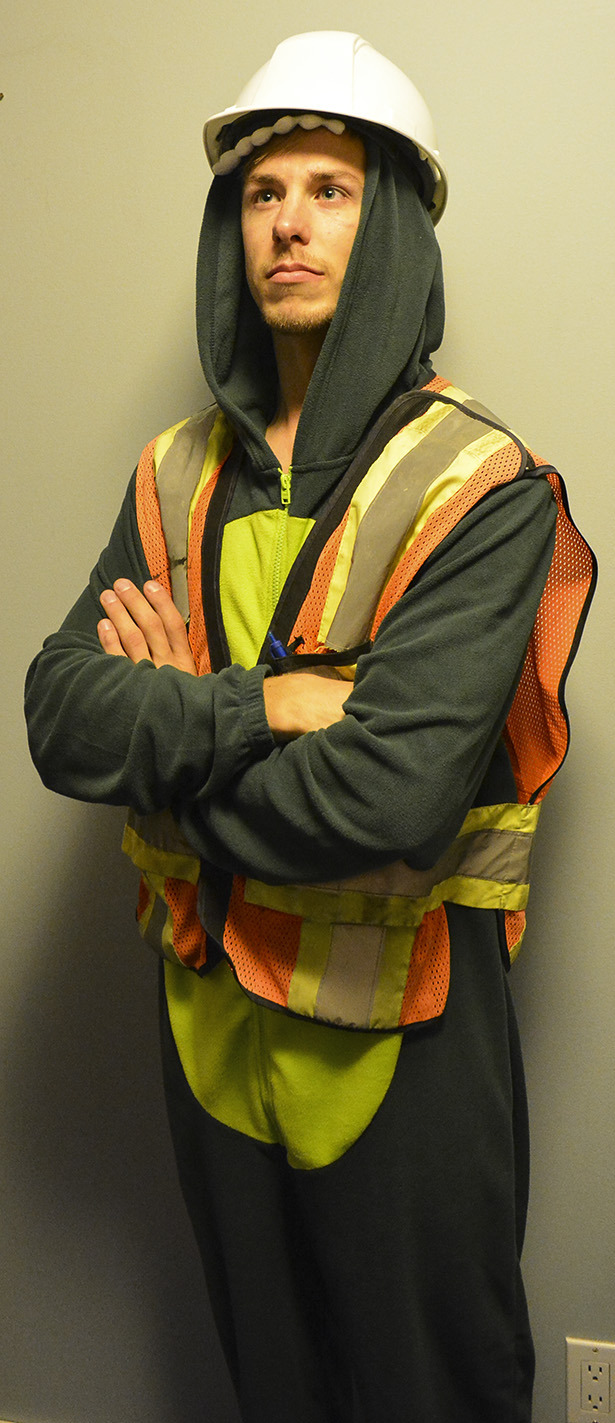 """Matt Matkin in his dinosaur """"onesie"""", wearing a safety vest and hard hat, emphasizing being safe on Halloween in Calgary on Wednesday, Oct. 22, 2014. Matkin is a Engineering Technician for Almor Testing Services. (Photo by Adrianna Thebault/The Press)"""