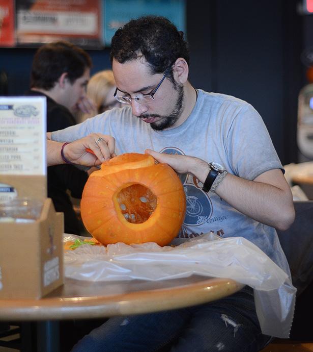 Deep concentration: Israel Maya, a first year business student, works on carving a Mexican skull into his pumpkin at the Gateway at SAIT in Calgary on Thursday, Oct. 30, 2014. Maya is from Mexico and had never carved a pumpkin before. (Photo by Angela Brown/The Press)
