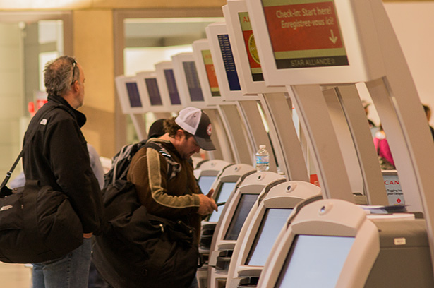 Travellers check in to their flights at electronic kiosks at the Calgary International Airport on Saturday, Nov. 8, 2014.  (Photo by Neil Reid/The Press)