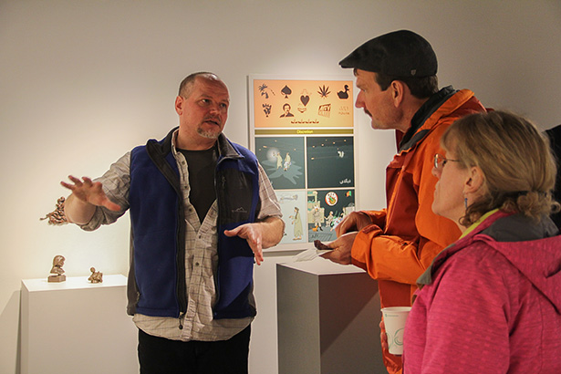 "Telling Rob's Story: Artist Al Henderson, left, explains his four-piece panel works entitled ""Rob's Story"" to gallery visitors Leslie Reinke and Kerrie Reinke, far right, at the Light Horse Tales of an Afghan War exhibit artist's reception."