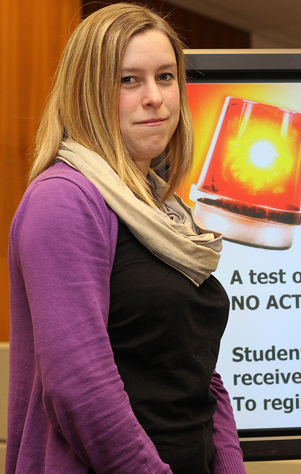 Information is Power: Melanie Simmons poses in front of a SAITVIEW screen showing the SAITALERT test screen. SAITVIEW screens are located across campus and work together with the SAITALERT notification as part of SAIT's emergency plan. (Photo by Evan Whitmore/The Press)