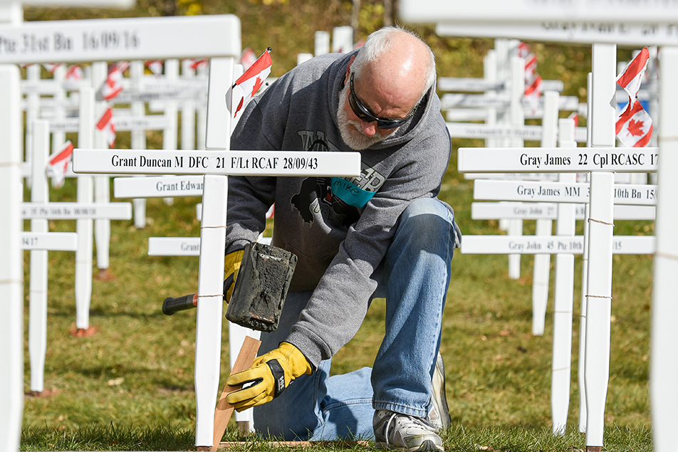 Field of Crosses: Mike Grant, a volunteer for the Field of Crosses Memorial Project, adjusts his uncle's cross at the site on Memorial Drive. The annual project features a cross for each soldier from southern Alberta who was killed while fighting for this country. (Photo by Elizabeth Cameron/The Press)