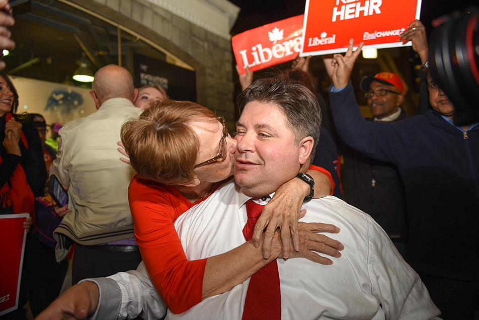 Victory Kiss: Liberal candidate Kent Hehr is congratulated for his victory in the riding of Calgary Centre after defeating Conservative incumbent Joan Crockatt in the federal election. Hundreds of liberal supporters turned out to support Kent Hehr on election night at the Bank & Baron Pub in downtown Calgary. (Photo by Tyler Marr/The Press)