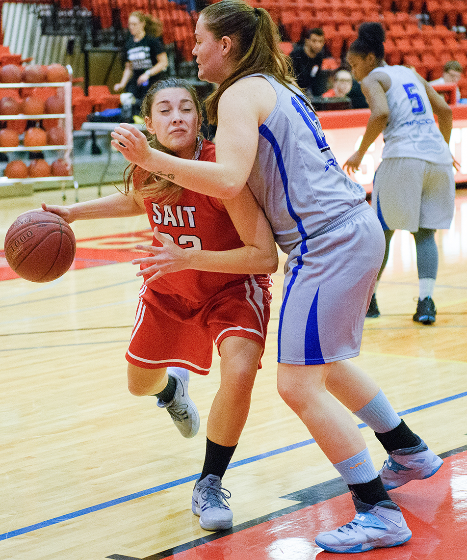 Court Battle: SAIT Trojan's player Jocelyn Skrilec goes for a layup but is cut short by a Keyano Huskies defender during ACAC basketball action at the SAIT gym. The Huskies lost to the Trojan's 68-55. (Photo by Adam F. Dullum/The Press)