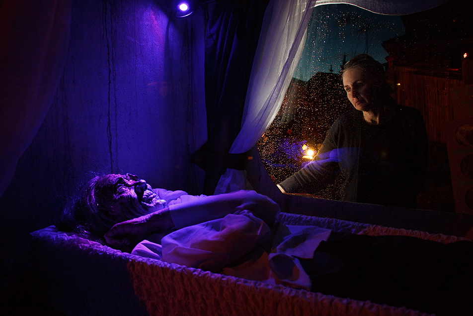 Haunted House Susan Neumann looks at a fake dead body in a carriage at The Coven, a haunted house in Northwest Calgary. The haunted house has been running every Halloween for about 25 years. (Photo by Joshua Neumann/The Press)