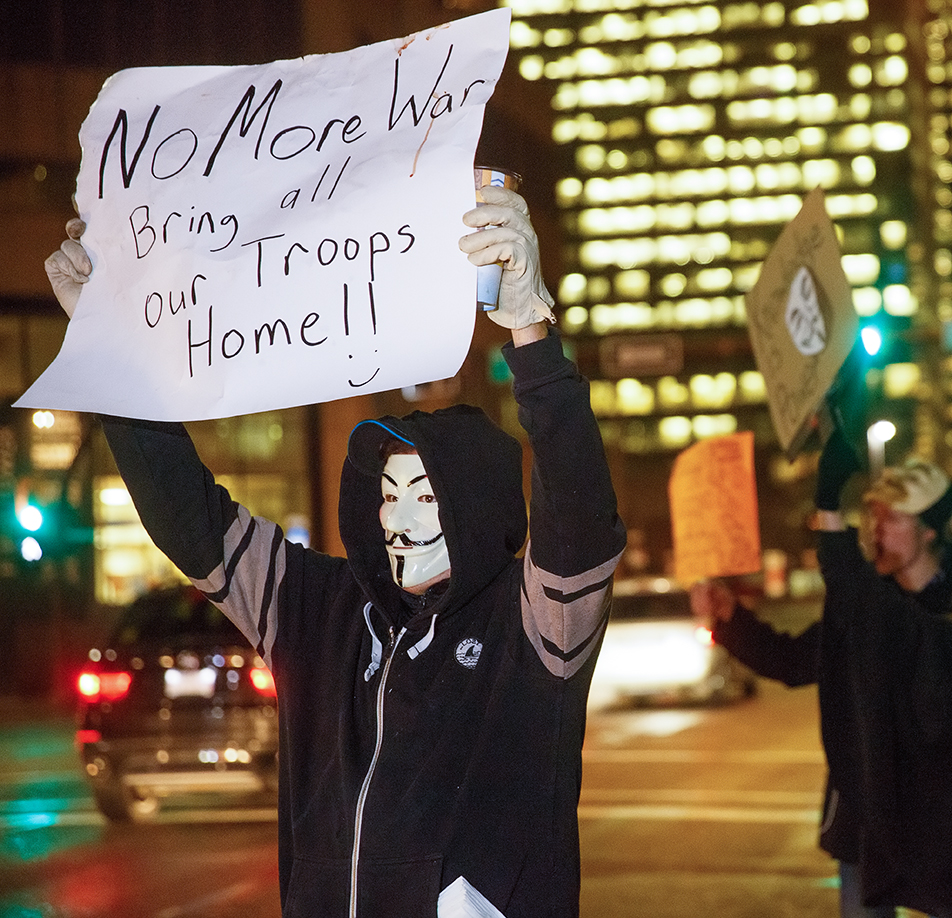 Protesting War: A protester holds up an anti-war sign outside the Harry Hays Building in Calgary on Thursday, Nov. 5, 2015. Every November, masked protesters take to the streets worldwide to voice their opinions on social and economic issues. (Photo by Liam Quinn/The Press)