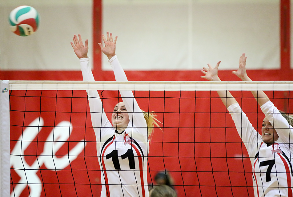 Big Block: SAIT Trojan's players Hayli Hinchey, left, and Samantha Carpenter go for a block during ACAC volleyball action against the Red Deer Queens at the Campus Centre in Calgary on Friday, Nov. 6, 2015. The Trojans defeated the Kings 3 sets to 2. (Photo by Kyle Meller/The Press)