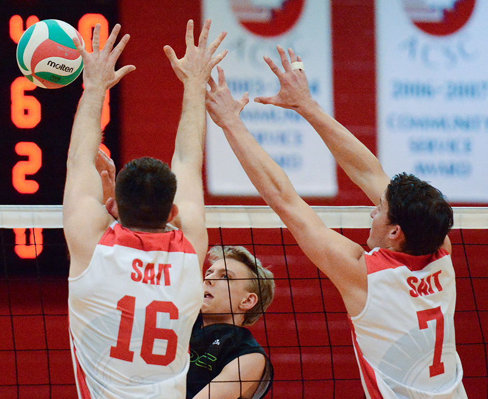 Double Block: SAIT Trojans middle Braedon Anderson, left, and leftside Spencer Coulter block a spike from Red Deer College power Brian Grenier, centre, during ACAC volleyball action at the SAIT Campus Centre gym on Friday, Nov. 6, 2015. The Kings took the match by a score of three sets to two. (Photo by Ryan Wellicome/The Press)