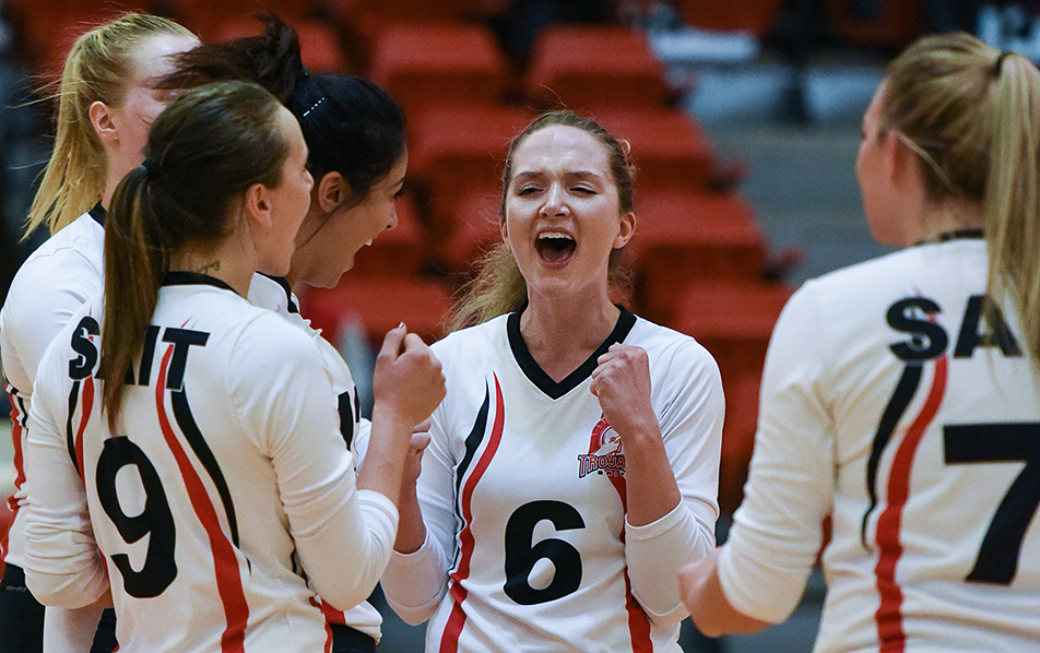 Big Score: SAIT Trojan's Chanelle Kayser, centre, celebrates with her teammates after the play during ACAC Women's volleyball action against the Red Deer Queens on Friday, Nov. 6, 2015. The Trojans won the match three sets to two. (Photo by Elizabeth Cameron/SAIT Polytechnic)