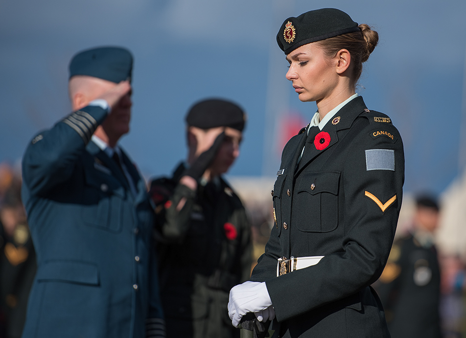 Standing Guard: A member of the 15 Field Ambulance division guards the stage of the Remembrance Day service at The Military Museum in Calgary on Wednesday, Nov. 11, 2015. Behind her, personnel salute after laying a wreath in honour of the Royal Canadian Navy. (Photo by Elizabeth Cameron/The Press)