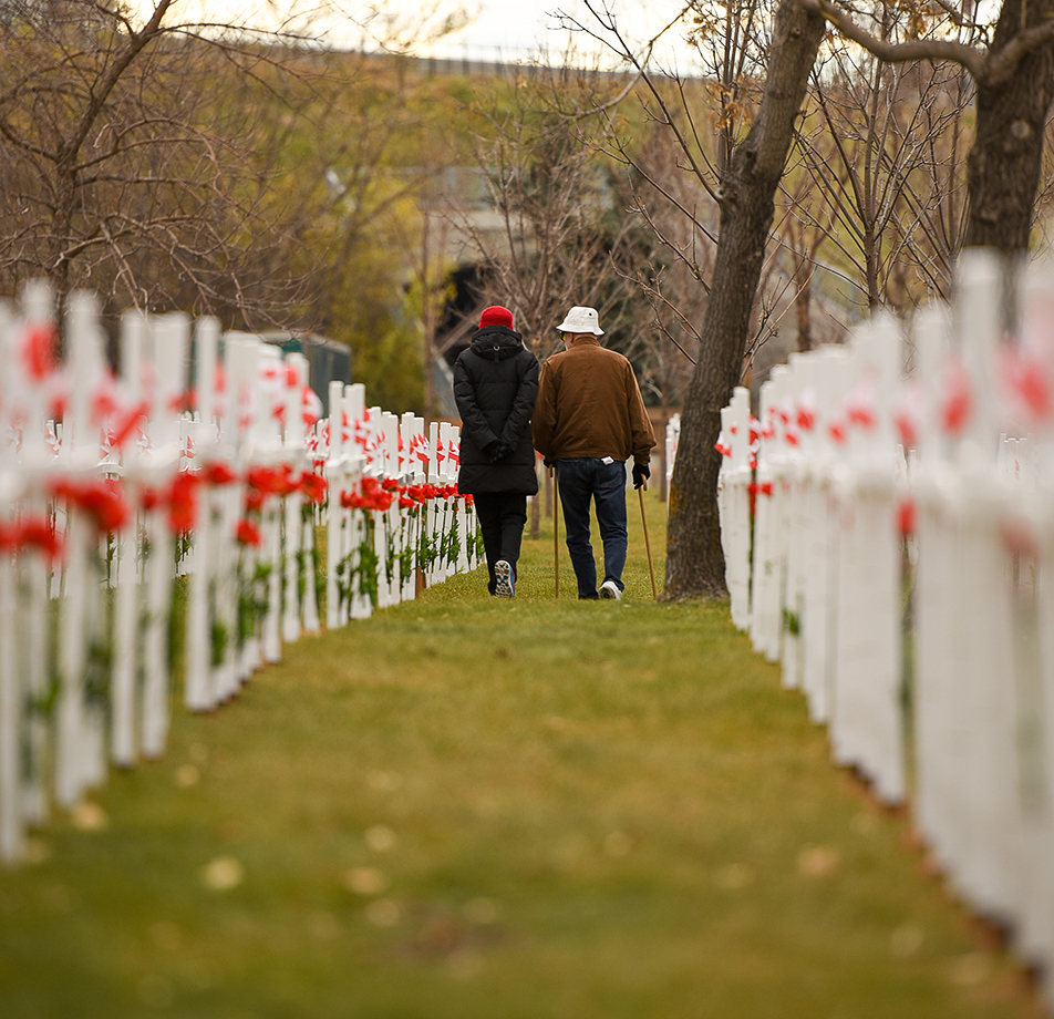Sombre Walk: A couple walk through the rows of crosses at the Field of Crosses Memorial project on Sunday, Nov. 1, 2015. Each cross is inscribed with the name, rank, regiment, date of death and age at death of a Southern Alberta soldier killed in action. (Photo by Tyler Marr/The Press)