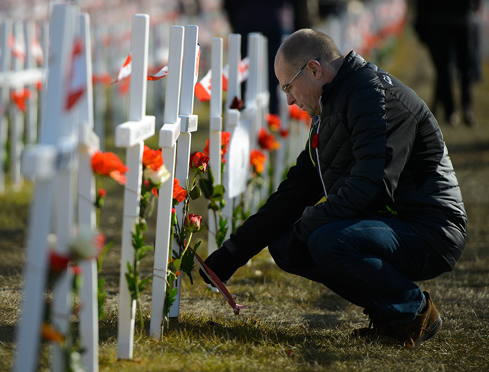 Paying Tribute: Red Bishop reads a fallen soldier's story off of a cross at The Field of Crosses Memorial Project along Memorial Drive in Calgary on Wednesday, Nov. 11, 2015. The Field of Crosses is a memorial created annually to honour those soldiers in Southern Alberta who lost their lives during WWI and WWII. (Photo by Andy Maxwell Mawji/The Press)
