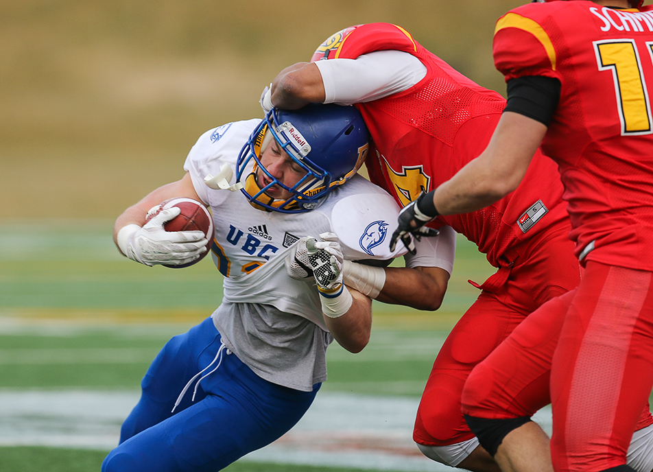 Ducking the Tackle: UBC Thunderbirds Ben Cummings, tailback, is tackled by U of C Dinos Robert Woodson, pensive back, during the Hardy Cup at McMahon Stadium on Saturday, Nov. 14, 2015. The final score was 31-26 for the Thunderbirds. (Photo by Kyle Meller/The Press)