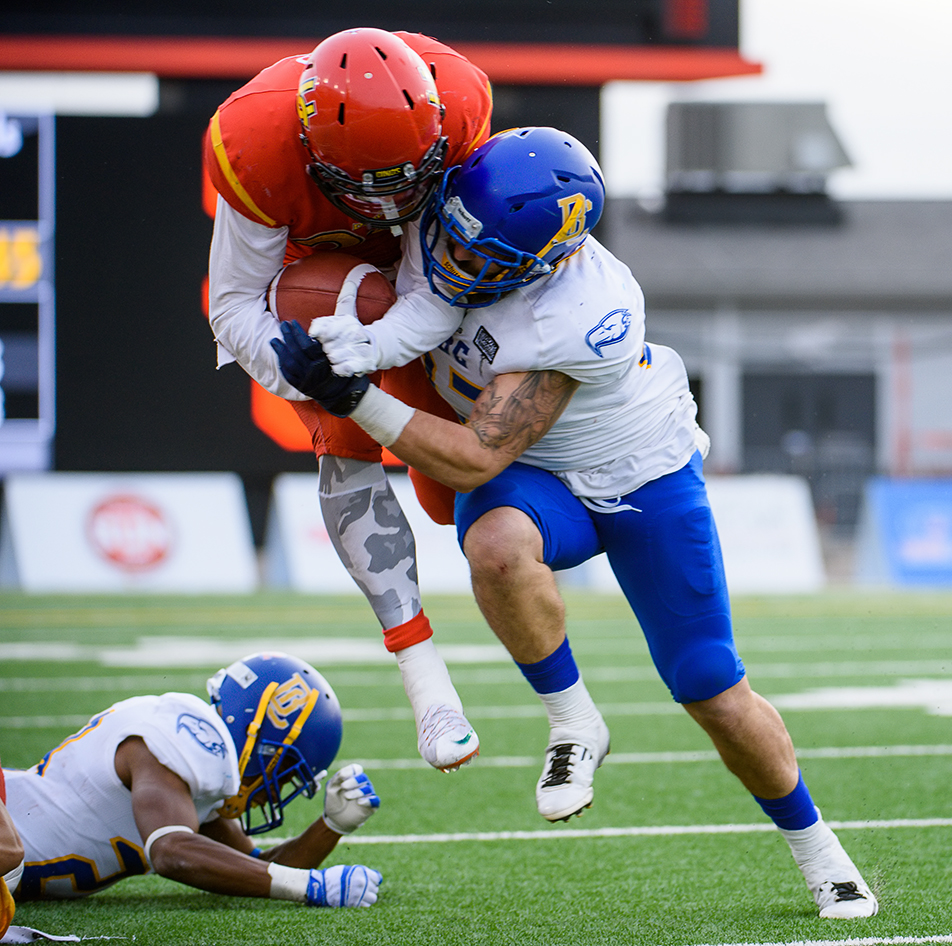 Big Tackle: U of C Dinos running back Mercer Timmis left, is tackled by UBC Thunderbirds linebacker Yanni Cabylis, right, during the Hardy Cup at McMahon Stadium on Saturday, Nov. 14, 2015. The final score was 31-26 for the Thunderbirds. (Photo by Brooke Hovey/The Press)
