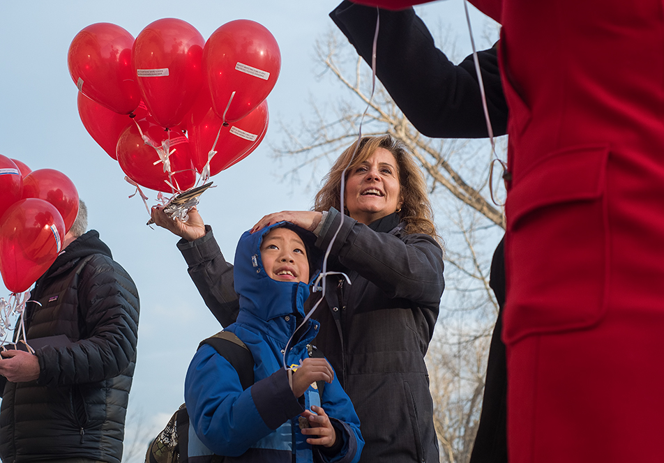 Balloons for Refugees: A student from Sunalta School receives a red balloon from teacher Katherine Papas at Sunalta School in Calgary on Monday, Nov. 23, 2015. The school handed out red balloons to raise awareness for the 1000 Schools Challenge, which asks 1000 schools across Canada to sponsor one refugee family each. (Photo by Elizabeth Cameron/The Press)