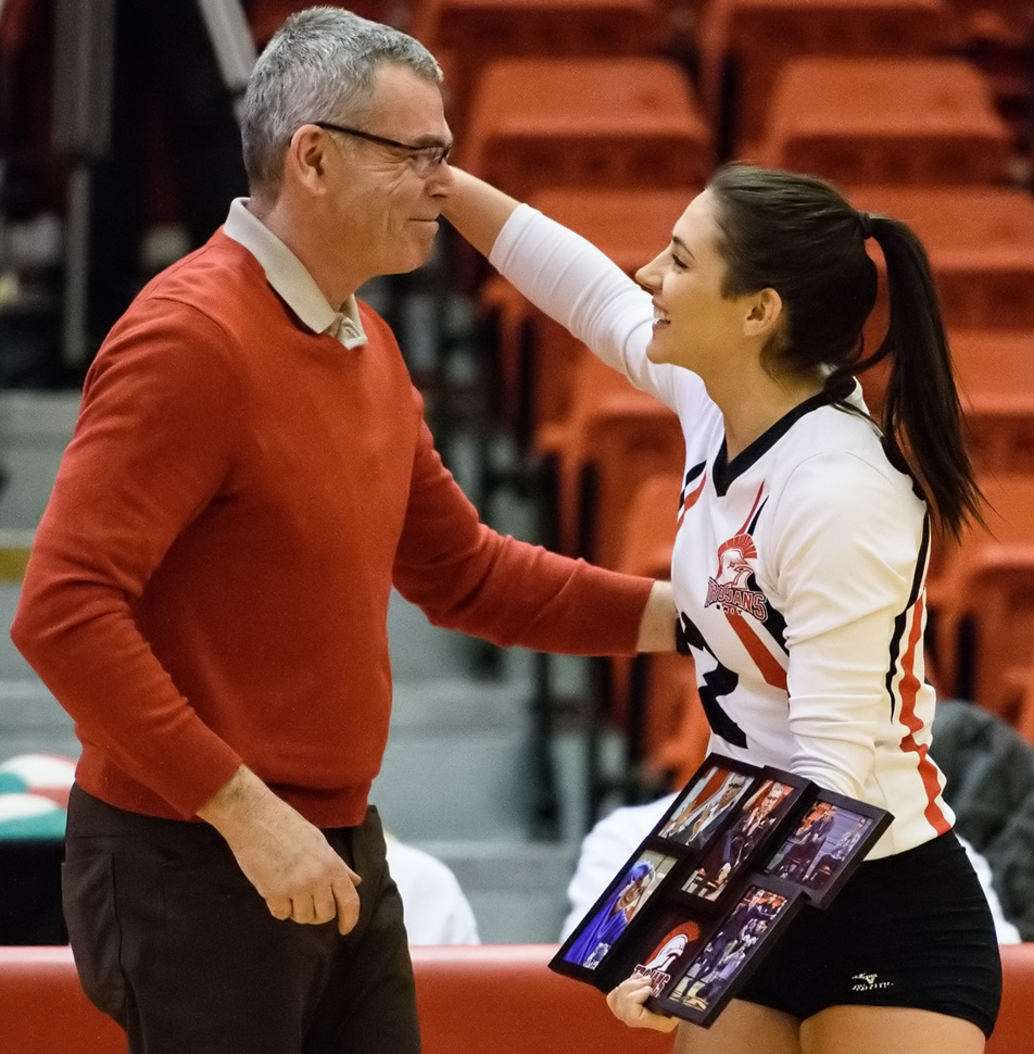 Accomplishment: Megan Brennan, right, congratulates SAIT Trojans women's volleyball head coach Art O'Dwyer before their game versus the Lethbridge College Kodiaks at the Campus Centre gym at SAIT in Calgary on Saturday, Jan. 30, 2016. O'Dwyer received a picture frame containing moments from his a career with the Trojans, in celebration of 100 games coached. (Photo by Vanessa Paterson/The Press)