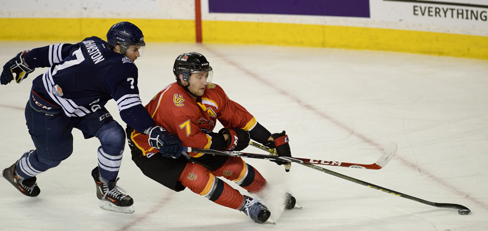 Dino Might : University of Calgary Dinos defenceman Max Ross, right, maintains control of the puck despite a close encounter from Mount Royal Cougars defenceman Mackenzie Johnston. Ross went on to score the winning overtime goal. (Photo by Kenneth Appleby/The Press)