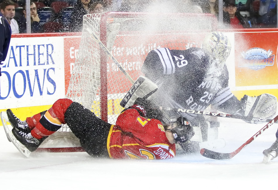 Ice Maker: Mount Royal Cougars goalie Cam Lanigan, right, receives an ice storm courtesy of University of Calgary Dinos forward Spencer Edwards. (Photo by Kyle Meller/The Press)