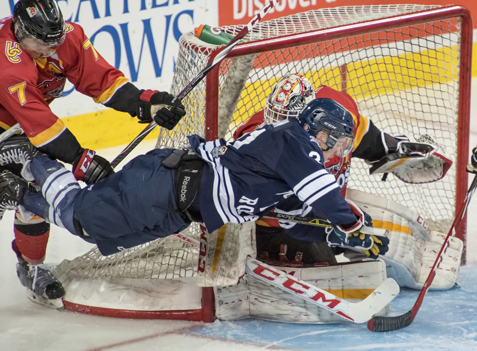 Dino Dump: Dinos defenceman Max Ross, left, shoves Cougars forward Connor Ranki. (Photo by Tyler Marr/The Press)