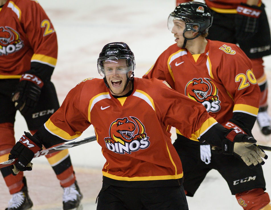 Dino Delight: Dinos forward Adam Kambeitz, centre, smiles with success after an overtime goal seals the victory against the Mount Royal Cougars. (Photo by Kenneth Appleby/The Press)
